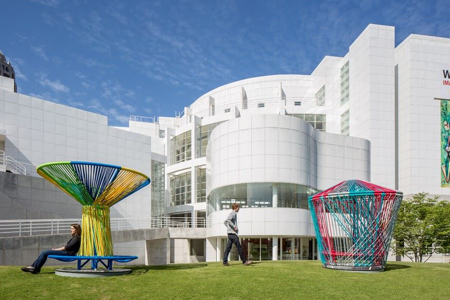 Outdoor picture of the High Museum of Art. Colorful rope sculptures are visible in the foreground.