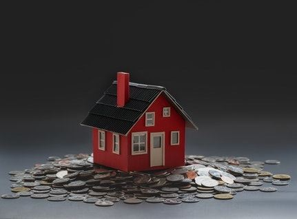 Red toy house placed on table on top of a pile of coins